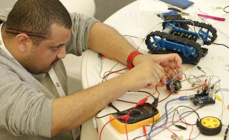 أحد الشباب المنهمكين في مشروع فريقه الابتكاري