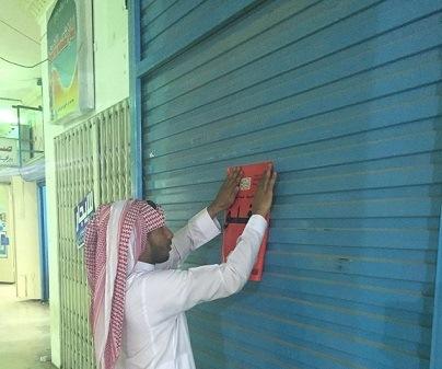 أحد المفتشين يضع ملصق مغلق أمام محل اتصالات
