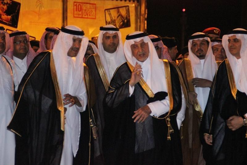 الأمير سلطان بن سلمان يناول هاتفه الجوال للأمير خالد الفيصل بعد ايقاف النابغة الذبياني الذي كان يلقي قصيدته أمام الحضور