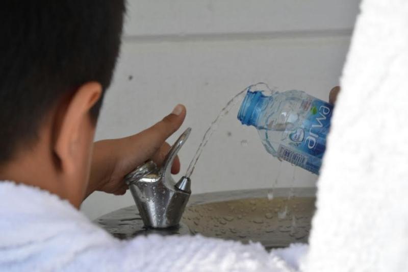 الحجاج يروون عطشهم ويبردون أجسادهم في الطريق إلى منى (332918088) 