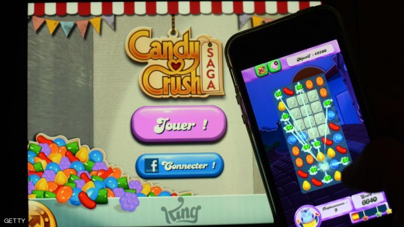 A man plays at Candy Crush Saga on his Iphone on January 25, 2014 in Rome. Candy Crush is one of the top online games developped by King.com.  AFP PHOTO / GABRIEL BOUYS        (Photo credit should read GABRIEL BOUYS/AFP/Getty Images)
