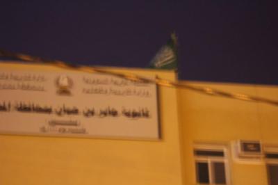 العلم السعودي ممزقاً على مبنى ثانوية في المجاردة