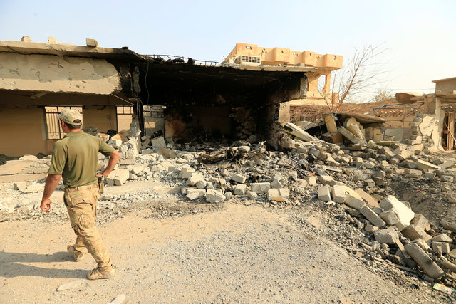 A member of Iraqi security forces walks past a destroyed building by clashes in Hammam al-Ali, south of Mosul, Iraq November 7, 2016. REUTERS/Thaier Al-Sudani