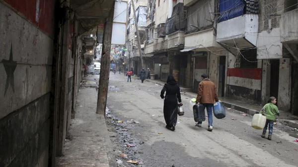 FILE - In this Feb. 11, 2016, file photo, civilians walk with containers for fuel and water in Aleppo, Syria. Syrian rescue worker says three civilians, a mother and two children, died in a suspected chlorine gas attack on an opposition-held district in the city of Aleppo. The report, which was posted online on Thursday, Aug. 11, could not be independently verified and it was not clear how it was determined that chlorine gas was released. (Alexander Kots/Komsomolskaya Pravda via AP, File)