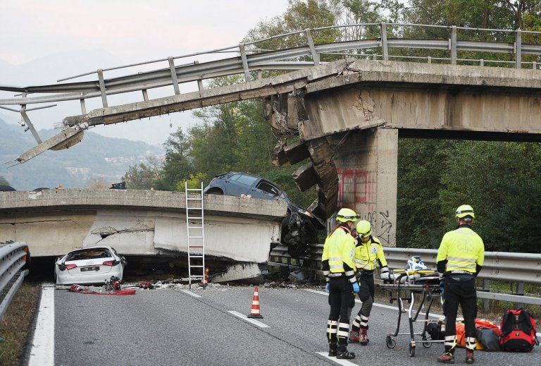 epa05607519 Italian emergency workers at the scene where one person was killed and four injured including three children when an overpass collapsed onto State Highway 36 between Milan and Lecco, Italy on 28 October 2016 sending an articulated lorry crashing down onto cars below.  EPA/FABRIZIO CUSA