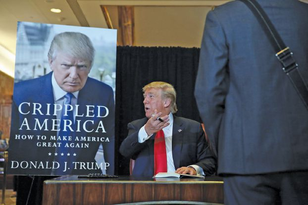 "NEW YORK, NY - NOVEMBER 03: Republican presidential candidate Donald Trump sign's his new book ""Crippled America: How to Make America Great Again,"" at the Trump Tower Atrium on November 3, 2015 in New York City. According to a new poll, Ben Carson, the retired neurosurgeon, has pulled ahead of Trump with 29% of Republican primary voters.   Spencer Platt/Getty Images/AFP == FOR NEWSPAPERS, INTERNET, TELCOS & TELEVISION USE ONLY =="