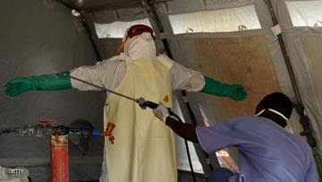 A nurse wearing personal protective equipment (PPE) is spayed with desinfectant before leaving the red zone at the Kenama ebola treatment center run by the Red Cross Society on November 15, 2014. Ebola-hit Sierra Leone faces social and economic disaster as gains made since the country's ruinous civil war are wiped out by the epidemic, according to a major study released on November 13. AFP PHOTO/ FRANCISCO LEONG        (Photo credit should read FRANCISCO LEONG/AFP/Getty Images)