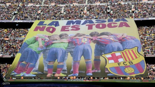 """Barcelona's supporters unveil a giant banner reading in Catalan """"La Masia, don't touch it"""" before the Spanish league football match FC Barcelona vs Real Betis at the Camp Nou stadium in Barcelona.  AFP PHOTO / JOSEP LAGO        (Photo credit should read JOSEP LAGO/AFP/Getty Images)"""