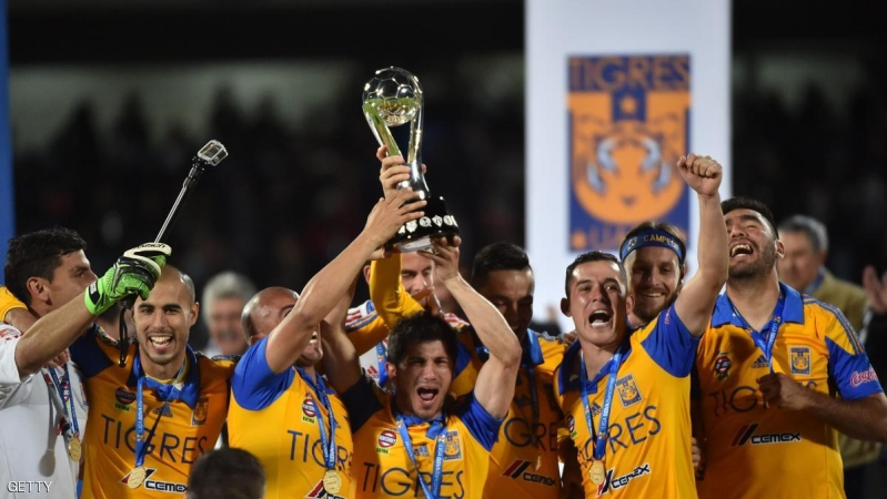 Tigres's footballers celebrate with the trophy after defeating Pumas  during their Mexican Apertura tournament football final match at the Olimpic stadium on December 13, 2015 in Mexico City.  AFP PHOTO/ Yuri CORTEZ / AFP / YURI CORTEZ        (Photo credit should read YURI CORTEZ/AFP/Getty Images)