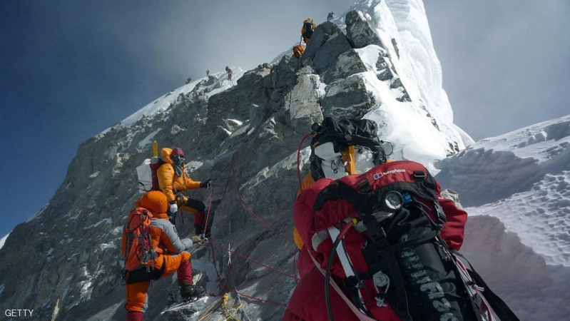 """FILE TO GO WITH Nepal-Everest-environment-climbing, FOCUS by Deepesh Shrestha  (FILES) In this May 19, 2009 file photograph, unidentified mountaineers walk past the Hillary Step while pushing for the summit of Mount Everest as they climb the south face from Nepal. A group of top Nepalese climbers is planning a high-risk expedition to clean up Everest, saying decades of mountaineering have taken their toll on the world's highest peak.  """"Everest is losing her beauty,"""" seven times Everest summitteer Namgyal Sherpa, 30, told AFP. """"The top of the mountain is now littered with oxygen bottles, old prayer flags, ropes, and old tents. At least two dead bodies have been lying there for years now."""" AFP PHOTO/COURTESY OF PEMBA DORJE SHERPA (Photo credit should read STR/AFP/Getty Images)"""