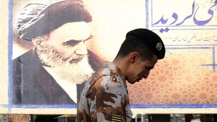 An Iranian soldier walks past a giant board displaying a portrait of the late founder of the Islamic Revolution Ayatollah Ruhollah Khomeini, as Iranians mark the start of 10 days of celebrations for the 37th anniversary of the Islamic revolution on February 1, 2016 at the Behesht-e Zahra (Zahra's Paradise) cemetery in southern Tehran.  / AFP / ATTA KENARE        (Photo credit should read ATTA KENARE/AFP/Getty Images)