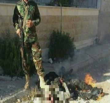 سوريا.. عنصر من حزب الله يحرق جثة ويتصور معها - المواطن