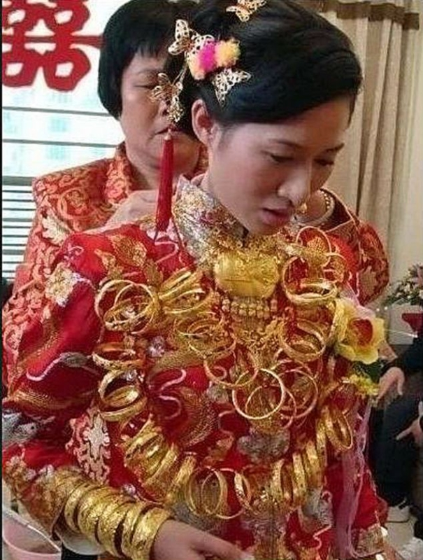 """Bride Liu Cheng wanted to look dazzling for her big day - and so she donned 200,000 GBP of solid gold jewellery to walk down the aisle. The one-woman Bling Dynasty - from Quanzhou, Fujian province, southern China - staggered to her groom with more than five kilos of necklaces, bracelets, gems, and rings dangling from her body. Proud mum Lin Hu - who spent more than an hour helping her 26-year-old daughter get into her jewellery - explained: """"I wanted to make the day as special as I could for my girl. She added: """"I've been collecting these pieces for years, and I got my relatives to do so as well because its important toshow her new relatives that she comes from a good family. """"We would save money and when the gold price was low we would buy - and sometimes when it was high we would sell to have cash to buy more gold later - it worked really well."""" One local wedding planner explained: """"Gold is seen as a sign of good luck and good fortune at a wedding and a sign that the  family of the bride is a good one - but this is right off the scale."""" Liu who gets to keep the gold said she might sell some of it - but would in any case in future only wear a few pieces at a time."""