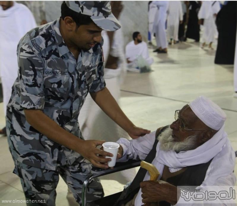رجل امن يساعد حاج من ذوي الاحتياجات