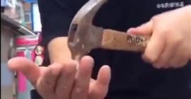 رجل يدق مسمارا في يده