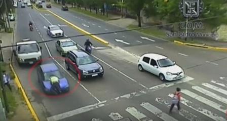 شرطي يتمسك بسيارة مخالفة لمسافة طويلة