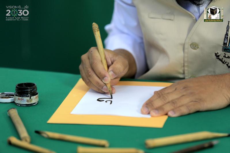 صورة توضح أحد العاملين وهو يقوم بكاتبة آيات من القران الكريم لتصميمها لكسوة الكعبة في مكة المكرمة