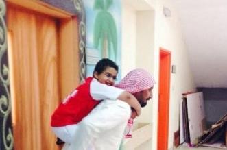 معلم يحمل طالب تربية خاصة على ظهره - المواطن