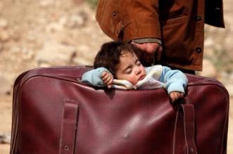 صورة مؤثرة لطفلة من الغوطة تنام داخل حقيبة والدها أثناء نزوحه - المواطن