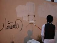 """طلاب جامعة الباحة و""""عاون"""" يزيلون الكتابات المشوهة للجدران"""