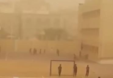 طلاب مدرسة يمارسون كرة القدم بغبار جدة