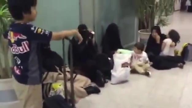 عائلة-تجلس-علي-الارض-بمطار-ينبع