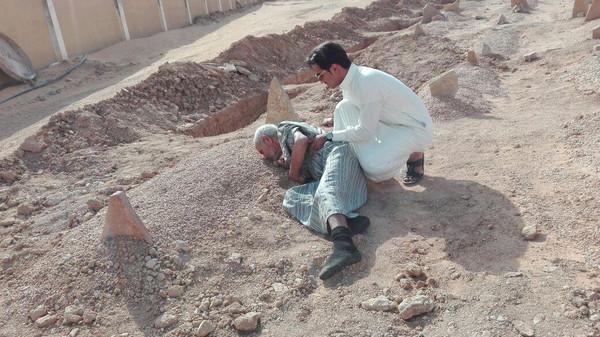 عجوز يقبل قبر زوجته (1)