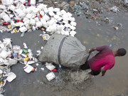 A man wades through a garbage filled water canal, pulling his bag after collecting empty bottles to sell in downtown of Port-au-Prince, Haiti, on February 28, 2016. Photo: AP
