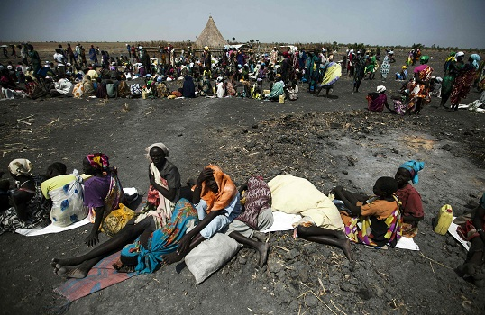 TOPSHOT - A large number of people wait for food air-drops by ICRC (International Committee of the Red Cross), outside Thonyor, in South Sudan, on February 3, 2016.  The village suffered armed clashes in October 2015. Fighting between Army forces and Sudan People's Liberation Movement in Opposition (SPLM-IO) took place following a brief takeover the neighbour town of Leer by rebel forces on October 2, 2015. Government forces pushed the rebels out later that day. The clashes were followed with intensive looting by armed men who entered humanitarian compounds and stole equipment, medical supplies and money.Thonyor is still under control of the opposition movement. / AFP / ALBERT GONZALEZ FARRAN