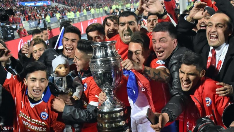 Chile's forward Eduardo Vargas (C) holds the trophy and celebrates after winning the 2015 Copa America football championship final against Argentina, in Santiago, Chile, on July 4, 2015. Chile won 4-1 (0-0).    AFP PHOTO / NELSON ALMEIDA        (Photo credit should read NELSON ALMEIDA/AFP/Getty Images)