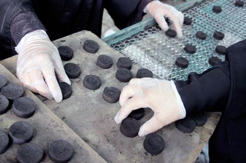 أيد نسائية ترص الفحم في عبوات (ندى الدهام)1
