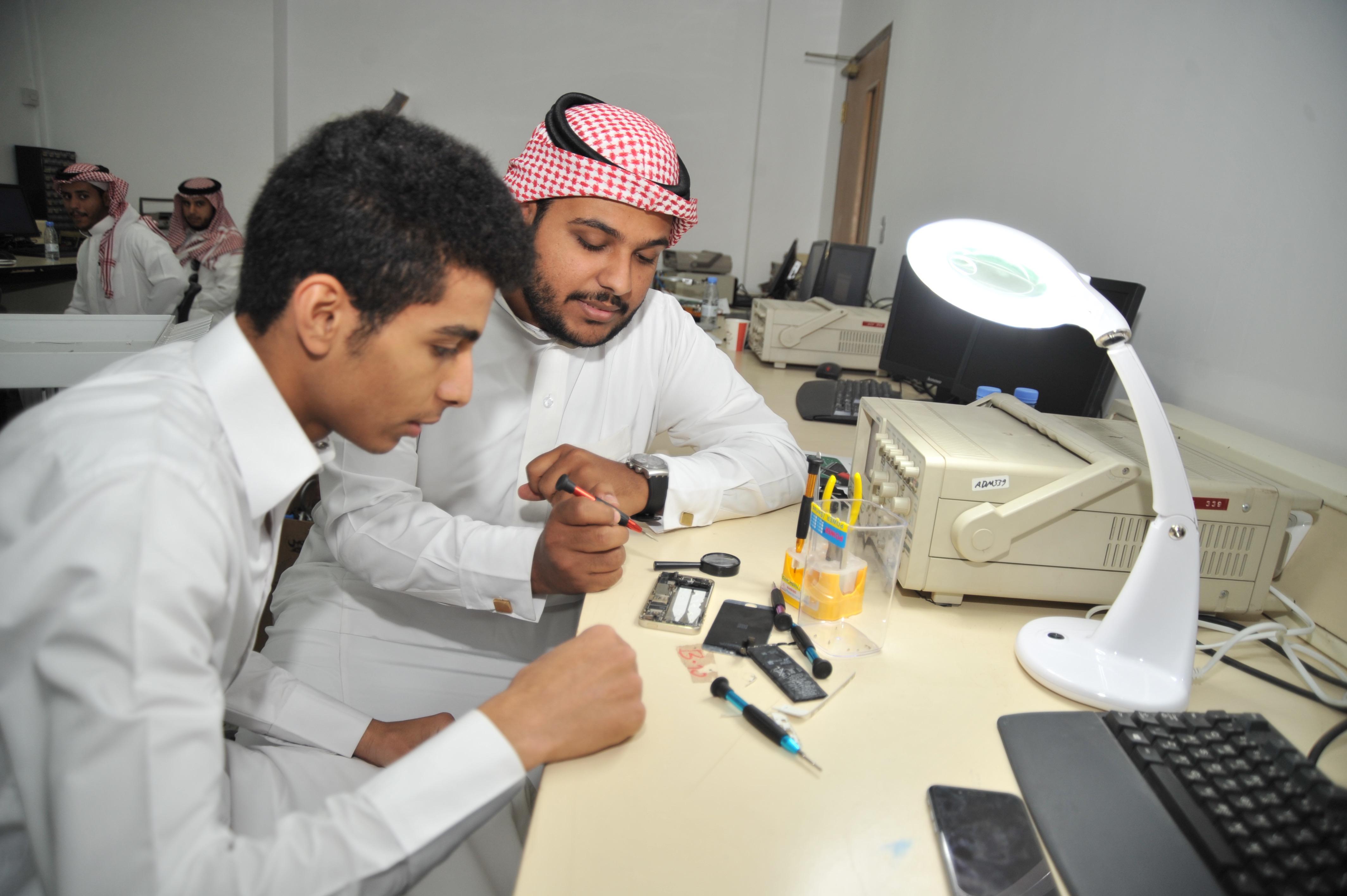 متدربان يقومان بصيانة جهاز جوال
