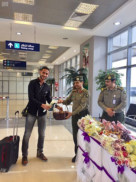 بالصور.. مدير جوازات جازان يستقبل المسافرين بالورود والحلوى - المواطن