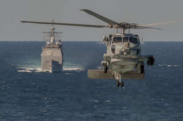 An MH-60R Seahawk helicopter assigned to the Swamp Foxes of Helicopter Maritime Strike Squadron (HSM) 74 flies in front of the guided-missile cruiser USS San Jacinto (CG 56). San Jacinto, part of the Harry S. Truman Carrier Strike Group, is conducting operations with units assigned to French Task Force 473 to enhance levels of cooperation and interoperability, enhance mutual maritime capabilities and promote long-term regional stability in the U.S. 5th Fleet area of responsibility. (U.S. Navy photo courtesy of the French navy by Chief Petty Officer Bruno Gaudry/Released)