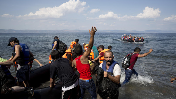 Migrants and refugees arrive on a dinghy after crossing from Turkey to Greece, as another one approaches the coast of Lesbos island, Tuesday, Sept. 8, 2015,.The island of some 100,000 residents has been transformed by the sudden new population of some 20,000 refugees and migrants, mostly from Syria, Iraq and Afghanistan. (AP Photo/Petros Giannakouris)