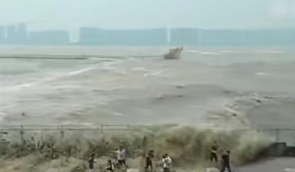 موجة مد عاتية تغمر المارة على ضفة نهر فى الصين