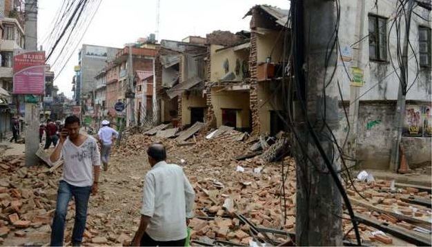 Nepalese people walk past collapsed buildings at Lalitpur, on the outskirts of Kathmandu on April 25, 2015.  A powerful 7.9 magnitude earthquake struck Nepal, causing massive damage in the capital Kathmandu with strong tremors felt across neighbouring countries.  AFP PHOTO / PRAKASH MATHEMA        (Photo credit should read PRAKASH MATHEMA/AFP/Getty Images)