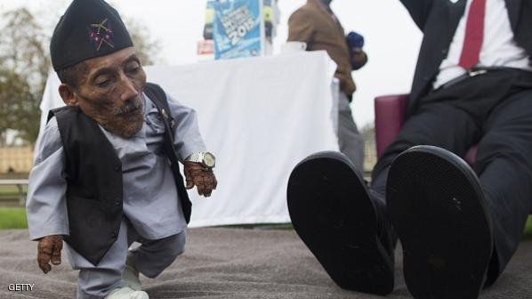 Chandra Bahadur Dangi, from Nepal, (L) the shortest adult to have ever been verified by Guinness World Records, walks past the feet of the world's tallest man Sultan Kosen from Turkey, during a photocall in London on November 13, 2014, to mark Guinness World Records Day. Chandra Dangi, measures a tiny 21.5in (0.54m)  the same height as six stacked cans of beans. Sultan Kosen measures 8 ft 3in (2.51m).  AFP PHOTO / ANDREW COWIE        (Photo credit should read ANDREW COWIE/AFP/Getty Images)