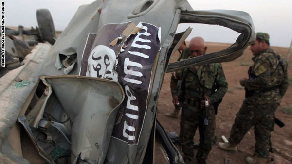 Peshmerga fighters inspect the remains of a car, bearing an image of the trademark jihadist flag, which belonged to Islamic State (IS) militants after it was targeted by an American air strike in the village of Baqufa, north of Mosul, on August 18,2014. Kurdish peshmerga fighters backed by federal forces and US warplanes pressed a counter-offensive Monday against jihadists after retaking Iraq's largest dam, as the United States and Britain stepped up their military involvement. AFP PHOTO/AHMAD AL-RUBAYE        (Photo credit should read AHMAD AL-RUBAYE/AFP/Getty Images)