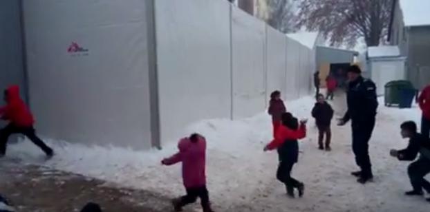 بالفيديو .. مقطع طريف لشرطي صربي يلاعب الأطفال اللاجئين بالثلج1
