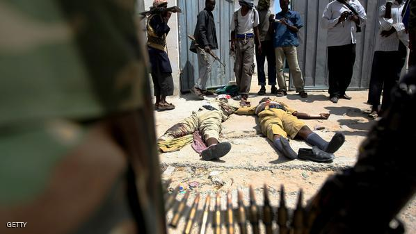 Fighters from Al-Shabab look at two dead