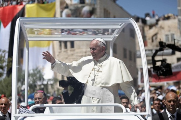 Pope Francis waves to the crowd as he arrives to lead an open-air mass in the Manger Square, next to the Nativity Church in the West Bank town of Bethlehem