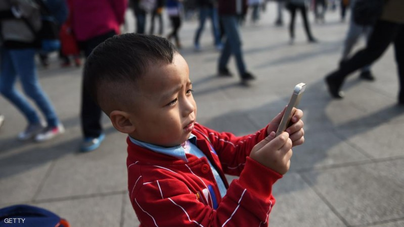 A young boy uses an iPhone to take photos in Tiananmen Square in Beijing on September 30, 2014. Apple said on September 30 it will begin selling its latest iPhones in China from October 17 after the Chinese regulator pressed the US giant to improve personal data security to gain approval. AFP PHOTO/Greg BAKER        (Photo credit should read GREG BAKER/AFP/Getty Images)