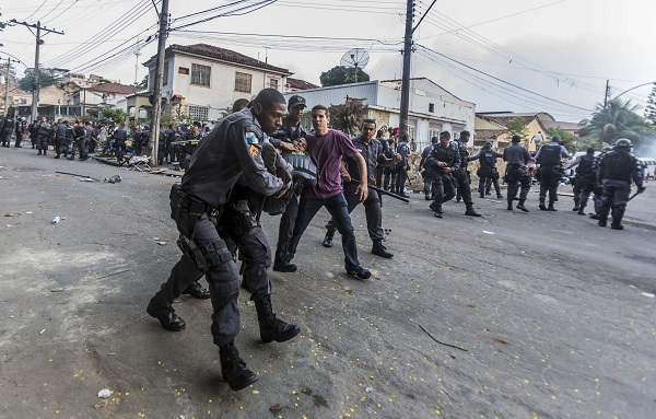 Policemen carry their colleague after he was injured when they attempted to repossess the land occupied by the Telerj slum in Rio de Janeiro
