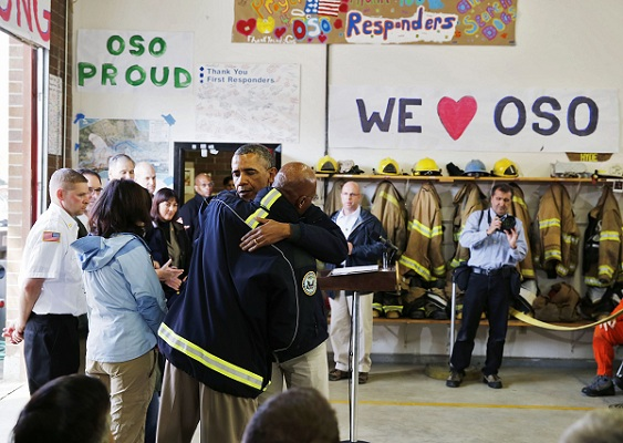 U.S. President Barack Obama hugs a first responder after touring the mud slide damage in Oso, Washington