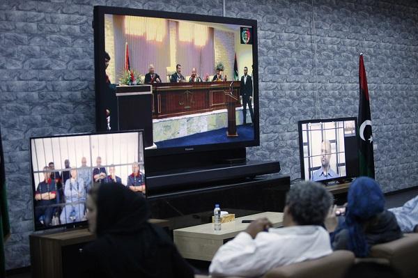 Journalists watch screens broadcasting the trial of Saif al-Islam Gaddafi in Tripoli