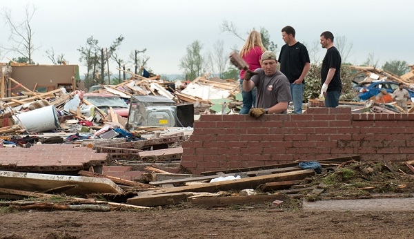 A man casts aside bricks while searching in the rubble of a destroyed house after a tornado hit the town of Vilonia, Arkansas