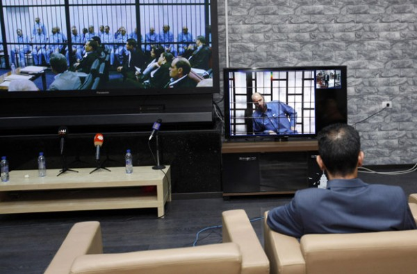 Man sits in front of two screens showing Saif al-Islam Gaddafi via video-link from a courtroom in Zintan, as well as former officials from Gaddafi government during a hearing at a courtroom in Tripoli