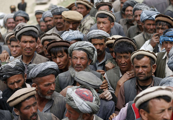 Afghan survivors wait for aid near the site of a landslide at the Argo district in Badakhshan province