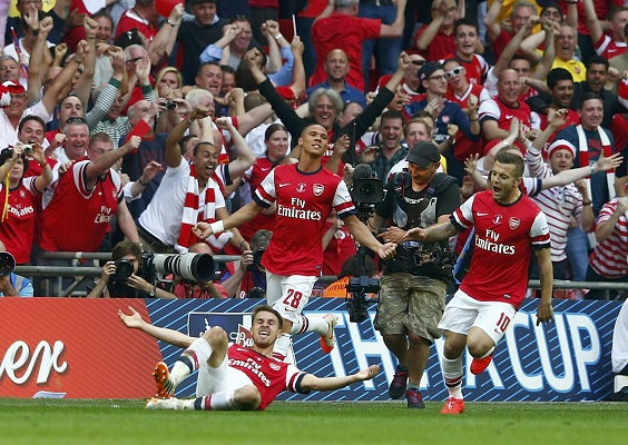 Arsenal's Ramsey celebrates with team mates Gibbs and Wilshere after scoring his team's third goal during their FA Cup final soccer match against Hull City at Wembley Stadium in London